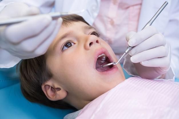 Schließen sie oben von zahnarzt, der ausrüstung hält, während junge untersucht