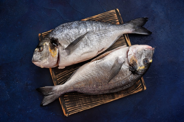 Schließen sie oben von zwei dorado-fischen auf einem schneidebrett und blauem hintergrund