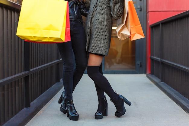 Schließen sie oben von zwei frauen mit den einkaufstaschen, die ihre beine zeigen.