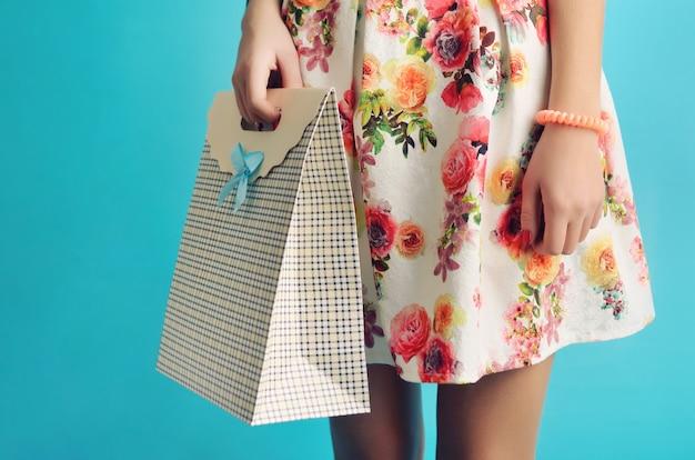 Schließen sie oben weibliche hände, die eine stilvolle karton-einkaufstasche auf blau halten