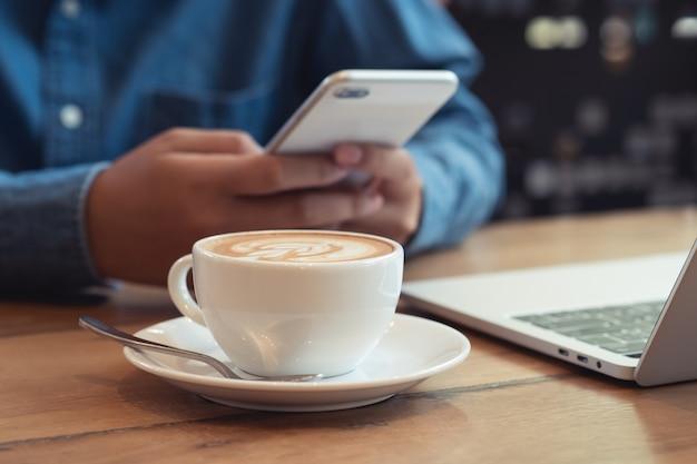 Schließen sie oben weiße kaffeetasse mit latte art auf holztisch. geschäftsmann, der das telefon im café benutzt