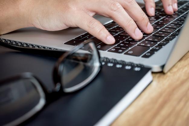 Schließen sie oben zu den händen eines geschäftstabletts etwas auf einem tablet-computer.
