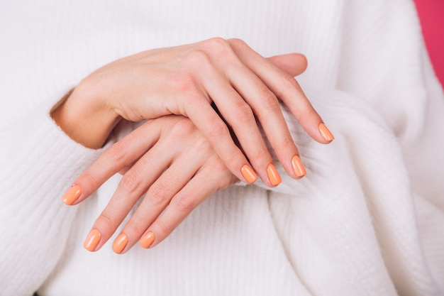 Schließen sie rahmen der frauenhände mit orange maniküre auf weißem pullover und rosa wand