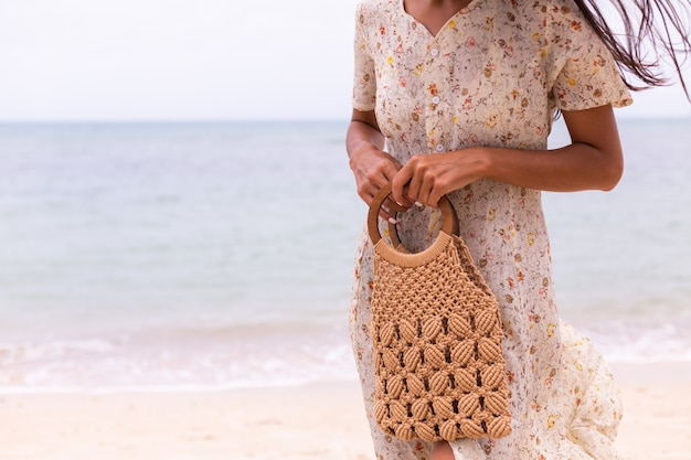 Schließen sie schuss der frau im leichten sommerfliegerkleid, das gestrickte tasche am strand, meer auf hintergrund hält.