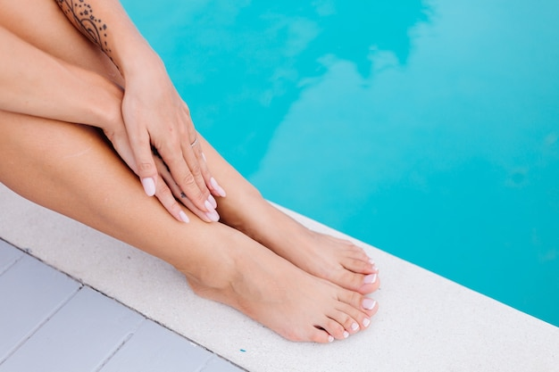 Schließen sie schuss frau füße und hände. frau sitzen am rand des blauen schwimmbades im urlaub