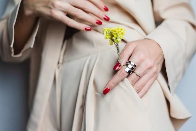 Schließen sie schuss von frau übergibt rote maniküre zwei ringe, die beige anzug tragen. gelbe niedliche getrocknete blume in der tasche.