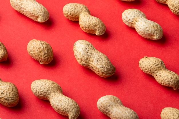 Schließen sie seitenansicht erdnüsse in der schale auf einem roten hintergrund