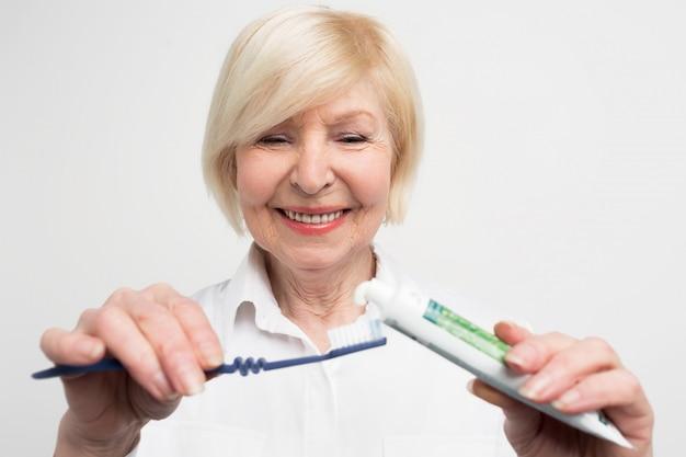 Schließen sie und schneiden sie vuew einer frau, die etwas zahnpasta auf die zahnbürste setzt. sie will ihre zähne putzen. die dame kümmert sich um ihren mund.
