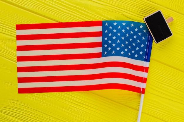 Schließen sie uns flagge und tafel draufsicht. gelber holztisch im hintergrund.
