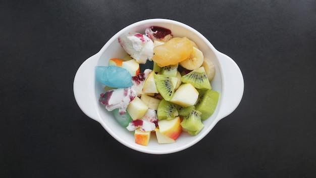 Schließen sie wüste mit frischem obst und eis. gemischte früchte mit eis und fruchteis auf schwarzer oberfläche