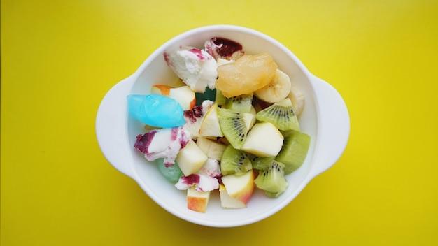 Schließen sie wüste mit frischem obst und eis. gemischte früchte mit fruchteis auf gelber oberfläche