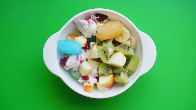 Schließen sie wüste mit frischem obst und eis. gemischte früchte mit fruchteis auf grüner oberfläche