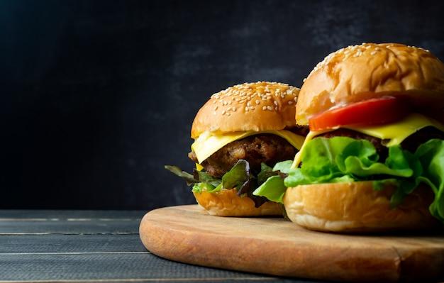 Schließen sie zwei frische leckere hausgemachte hamburger mit frischem gemüse