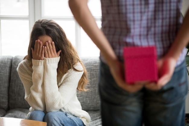 Schließende augen der jungen frau mit den händen, die auf anwesende überraschung warten
