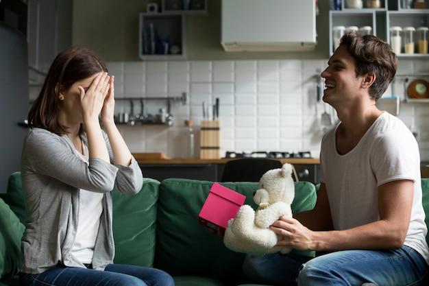 Schließende augen des liebevollen ehemanns der frau, die romantisches überraschungsgeschenk darstellt