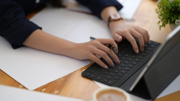 Schließt herauf weibliche hand unter verwendung der digitalen tablettenberechnung
