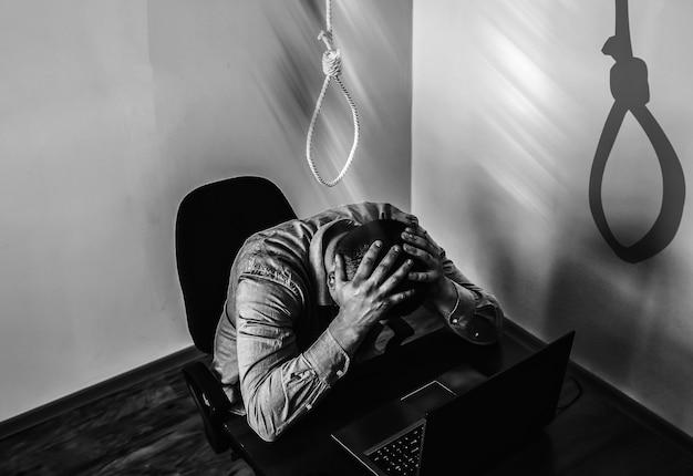 Schlinge ist über dem büroangestellten. selbstmord-konzept. hängen wegen arbeitsstress. burnout-depression. schreckliche lebenssituation. mann nahe dem laptop am schreibtisch