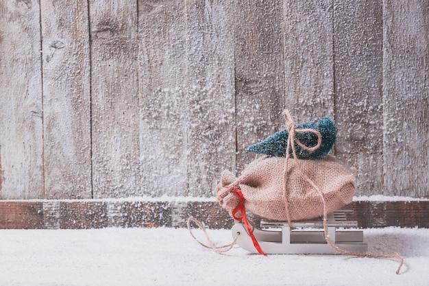Schlitten mit einem geschenkbeutel und einer kiefer oben
