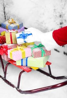 Schlitten mit weihnachtsgeschenken, auf winterhintergrund