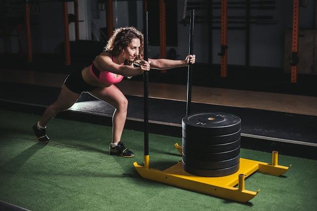 Schlittenschubfrau, die gewichte beim training drückt