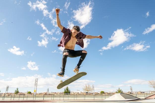 Schlittschuhläufer mit dem skateboard, das trick im rochenpark tut