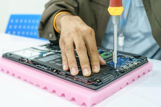 Schlosser, der laptop motherboard auseinanderbauen. it-techniker, der gebrochenes laptopnotizbuch repariert