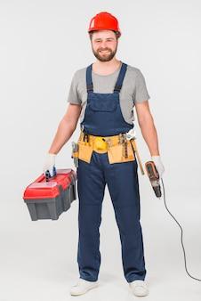 Schlosser, der mit werkzeugkasten und bohrgerät steht