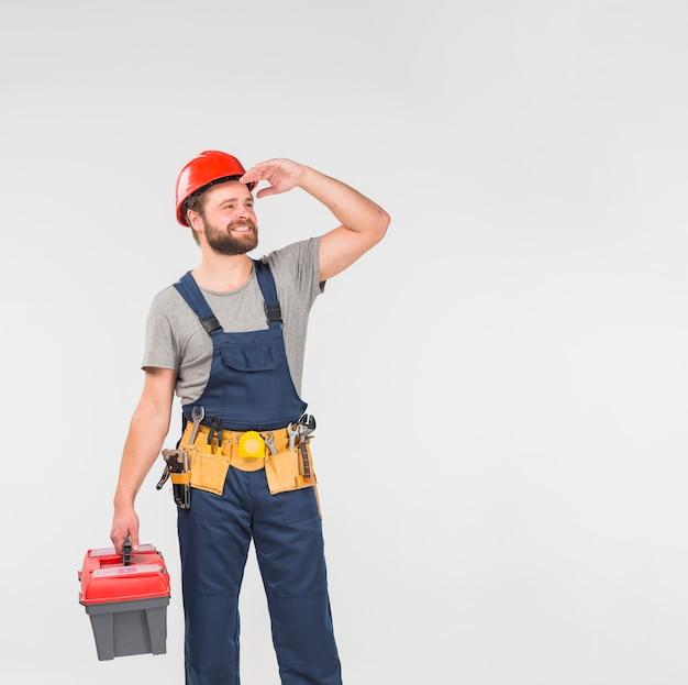 Schlosser im blauen overall mit dem werkzeugkasten, der weg schaut