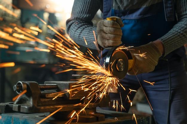 Schlosser in spezialkleidung und schutzbrille arbeitet in der metallbearbeitung mit winkelschleifer
