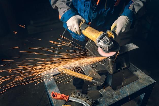 Schlosser in spezialkleidung und schutzbrille arbeitet in der produktion. metallbearbeitung mit winkelschleifer. funken in der metallbearbeitung.