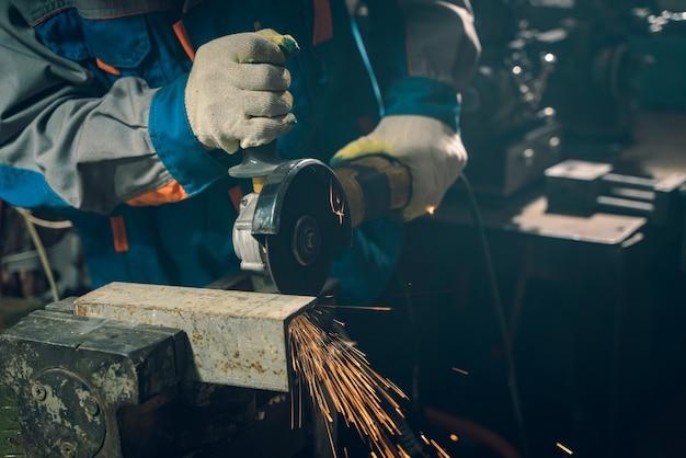 Schlosser in spezialkleidung und schutzbrille arbeitet in der produktion. metallbearbeitung mit winkelschleifer