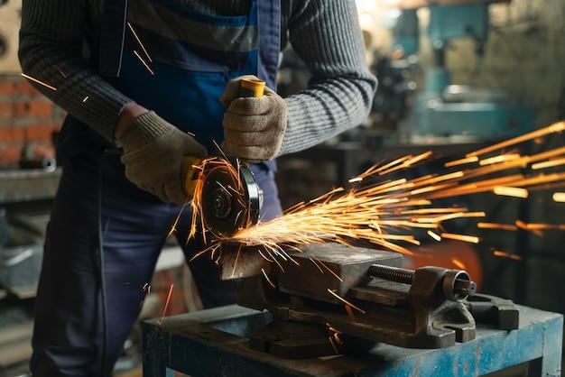 Schlosser in spezialkleidung und schutzbrille arbeitet in der produktion. metallbearbeitung mit winkelschleifer Premium Fotos