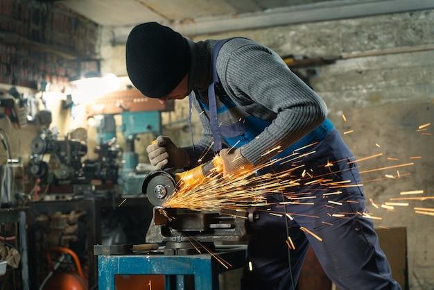 Schlosser in spezialkleidung und schutzbrillen arbeitet in der produktion metallbearbeitung mit winkelschleifer