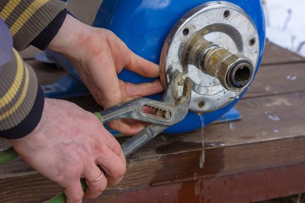 Schlosser klempner, der den wassersystemausdehnungsbehälter repariert