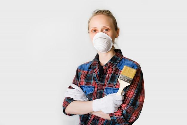 Schlosser, zimmermann, lohnarbeiter, frau oder mädchen in schutzhandschuhen und maske hält einen neuen sauberen pinsel, schaut in zelle. das konzept der haus- und berufsreparatur, aufbau.
