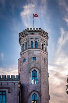 Schlossturm mit fliegender lettischer flagge. vecauce manor bei sonnenuntergang.
