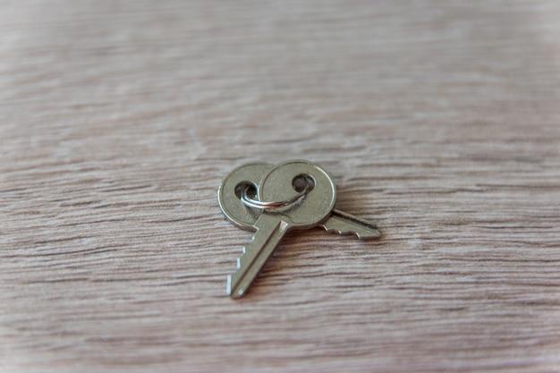 Schlüssel auf dem hölzernen hintergrund.