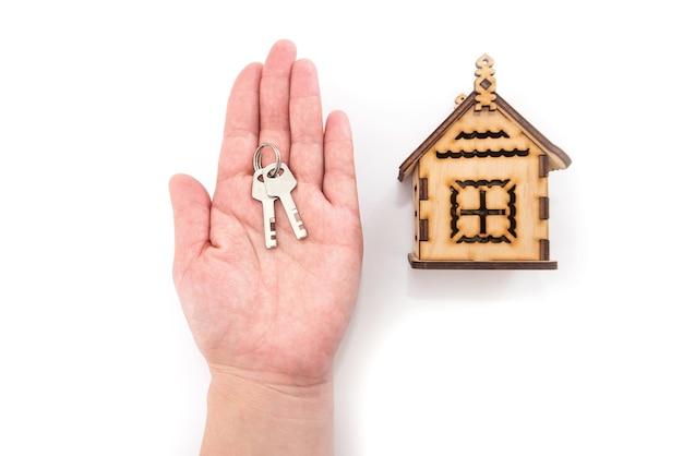Schlüssel auf der handfläche einer frau und einem holzhaus auf einem weißen hintergrund.