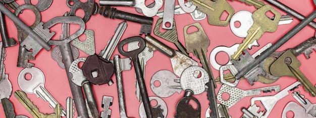 Schlüssel auf rosa hintergrund gesetzt. türschlossschlüssel und safes für eigentumssicherheit und hausschutz. verschiedene antike und neue schlüsseltypen.