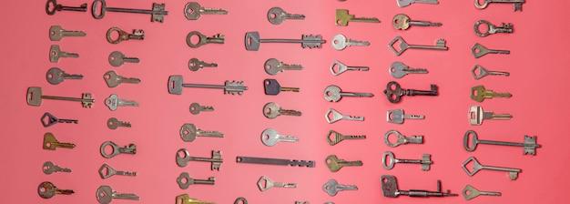 Schlüssel auf rosa hintergrund gesetzt. türschlossschlüssel und safes für eigentumssicherheit und hausschutz.