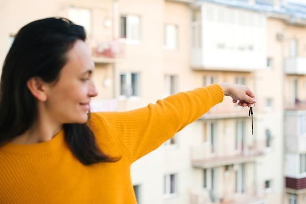 Schlüssel aus neuer wohnung gegen hochhaus. frau, die schlüssel zu einer neuen wohnung hält. immobilienbranche. glücklicher wohnungseigentümer, der schlüssel über neubau zeigt. zeit für den kauf von immobilien.