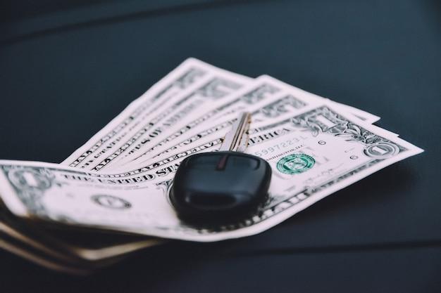 Schlüssel des autos auf straßen- und dollargeld für tägliche einkaufsweinlese