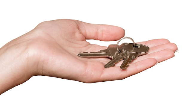 Schlüssel in den händen einer jungen frau auf einem weißen isolierten hintergrund