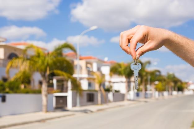 Schlüssel in der hand für neues zuhause und immobilienkonzept von einweihungsmieter und neues haus