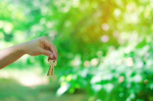 Schlüssel in der hand im park draußen. konzept von immobilien. verkauf und kauf einer wohnung