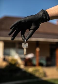 Schlüssel in der hand in schwarzem handschuh. verwenden sie alkoholspray, um das koronavirus zu bekämpfen und keime am schlüssel des hauses oder büros regelmäßig abzutöten. covid-19-ncov- oder coronavirus-quarantänekonzept.