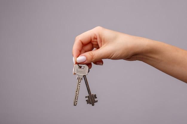 Schlüssel in der hand lokalisiert auf grau