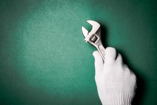 Schlüssel in der hand mit schutzhandschuh auf grünem hintergrund. freier platz für text
