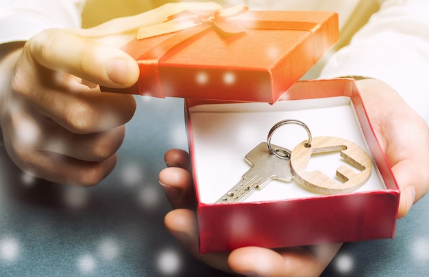 Schlüssel mit einem haus mit einer geschenkbox und einem schnee. tolle angebote für immobilien in der wintersaison.