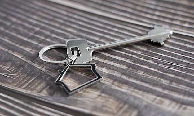 Schlüssel mit hausikone auf dem hölzernen hintergrund